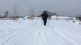 Mature Ukrainian man with two handmade wooden walking sticks moving on a winter road in Ukrainain village stock footage