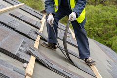 Workman install tile on roof of new house under construction royalty free stock photo