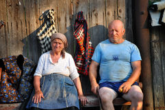 Mature villagers resting on a wooden bench Royalty Free Stock Images