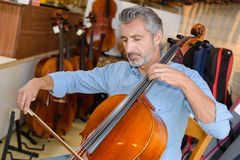 Mature violin maker while testing violins in laboratory Royalty Free Stock Photography