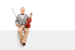 Mature violinist sitting on a panel. Mature violinist holding an acoustic violin and sitting on a blank signboard isolated on white background Royalty Free Stock Photos