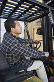 Mature Warehouse Worker Driving Forklift Stock Photography