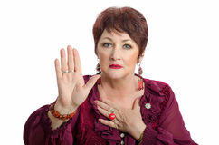 Mature wary woman posing with raised right hand Royalty Free Stock Images