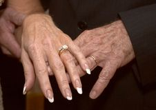 Mature Wedding Hands 2. A closeup of the hands of a newly married, mature couple, displaying their wedding bands Stock Photo