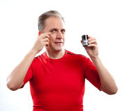 Mature well groomed man cares of the appearance - uses  against wrinkles cream Royalty Free Stock Photo