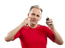The mature well-groomed man cares of the appearance - uses  against wrinkles cream Royalty Free Stock Photos