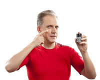 The mature well-groomed man cares of the appearance - uses  against wrinkles cream Stock Photography