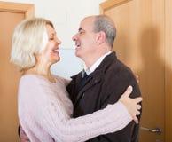 Mature wife meeting husband near door. Happy senior women hugging elderly boyfriend at doorway and smiling Royalty Free Stock Images