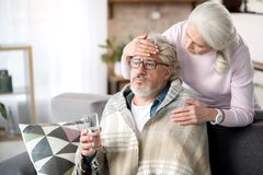 Mature wife taking care of her ill spouse. You have temperature, darling. Careful senior women is touching forehead of her sick husband by hand. Sad men is Stock Image