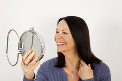 Mature woman. A mature woman looking into a mirror for beauty and make-up Stock Image