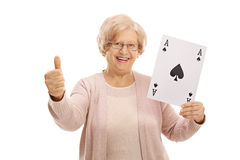 Mature woman with ace of spades card making thumb up. Joyful mature woman showing an ace of spades card and making a thumb up gesture isolated on white Stock Photo