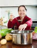 Mature woman adding seasoning into lent diet soup Stock Photo