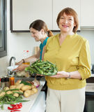 Mature woman and adult daughter cooking vegetables Stock Photo