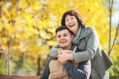 Mature woman with adult son in the autumn park royalty free stock image