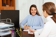Mature woman answering questions of employee Stock Image