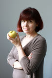 Mature Woman with an Apple Royalty Free Stock Images