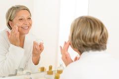 Mature woman apply cream looking bathroom mirror. Senior woman looking in bathroom mirror and applying anti-wrinkles cream stock image