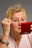 Mature woman applying eye-shadow Royalty Free Stock Photo