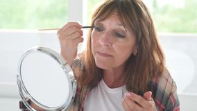 Mature woman applying eyeshadow with a brush stock footage