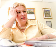 Mature Woman stressed at desk Royalty Free Stock Photography