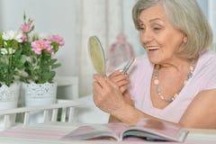 Mature woman applying lipstick Stock Images