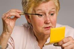 Mature woman applying mascara Royalty Free Stock Photography