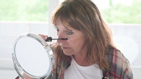 Mature woman applying mascara on eyelashes stock video footage