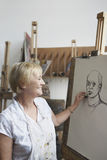 Mature Woman In Art Class. Side view of a smiling mature woman in art class royalty free stock photography