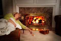 Mature woman asleep by fire royalty free stock photo
