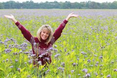 Happy Mature woman in flower field Royalty Free Stock Images