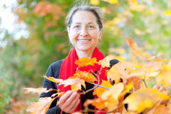 Mature woman in autumn with maple leaves Royalty Free Stock Photography