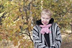 Mature woman at autumn oak Royalty Free Stock Photography