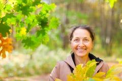 Mature woman  in autumn park Stock Photos