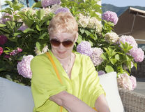A mature woman on the background of Hydrangeas Royalty Free Stock Images