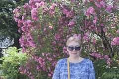 A mature woman on a background of oleander Royalty Free Stock Photography