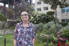 A mature woman on a background of variety of flowers Royalty Free Stock Photo