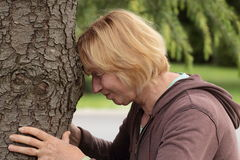 Mature woman banging head against tree Stock Photo