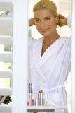 Mature woman in bathrobe adjusting hair, smiling, view through shutters Royalty Free Stock Images