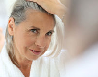 Mature woman in bathrobe looking hair Royalty Free Stock Images