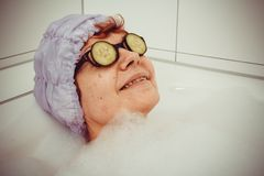 Mature woman in bathtub with cucumber slices on glasses Stock Photos