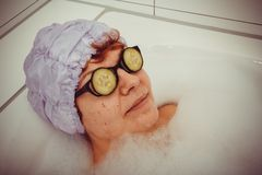 Mature woman in bathtub with cucumber slices on glasses Stock Photography
