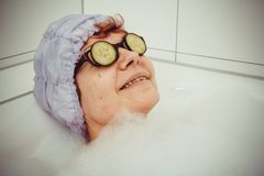 Mature woman in bathtub with cucumber slices on glasses Royalty Free Stock Photos