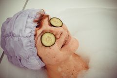 Mature woman in bathtub with cucumber slices Stock Image