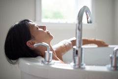 Mature woman in a bathtub Stock Image