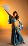 Mature woman in belly dance with fan Stock Photo