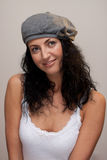 Mature woman in a beret. Attractive happy smiling mature woman in beige beret on Gray background Royalty Free Stock Images
