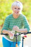 Mature woman with bicycle Stock Image