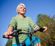 Mature woman with bicycle Royalty Free Stock Photo