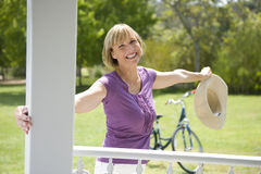 Mature woman with bicycle and hat leaning from post, smiling, portrait royalty free stock images