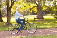 Mature woman bike. Beautiful mature woman riding a bike at the park Stock Image